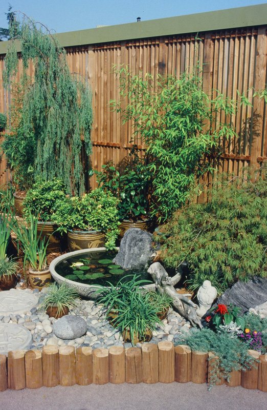 backyard landscaping with fence and pond